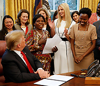 "United States President Donald J. Trump listens as Ella Zande, a Peace Corps beneficiary from Malawi makes remarks prior to his signing the National Security Presidential Memorandum to Launch the ""Women's Global Development and Prosperity"" Initiative in the Oval Office of the White House in Washington, DC on Thursday, February 7, 2019.  Pictured at center is First Daughter and Advisor to the President Ivanka Trump.<br /> Credit: Martin H. Simon / CNP/AdMedia"