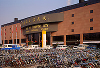 China, Beijing.  Modern shopping mall/center/centre, Shopping City, with hundreds of bicycles/bikes parked outside.