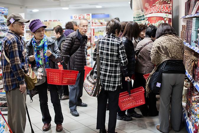 Japanische Touristen decken sich in einem Supermarket mit günstigen Spekulatius und dalmatinichen Rotwein ein. Die Preise in Bosnien sind günstiger als in Kroatien. Zahlreiche Touristen halten in Neum an, um günstig einzukaufen. Transittouristen sind ein wesentlicher Wirtschaftfaktor für den Einzelhandel in Neum. Der kleine Ort Neum liegt in Bosnien-Herzegovina und bildet den einzigen Zugang zum Meer des Balkanlandes. Auf einer Länge von 9 km durchschneidet der Ort das kroatische Staatsgebiet (Neum-Korridor) Seit dem EU-Beitritt Kroatiens ist Neum auf beiden Seiten von EU-Außengrenzen eingeschlossen. /  Japanese Tourist buy tea cake and Dalmatian Red wine in a supermarket. Since Bosnian prices are much cheaper then in Croatia,  a lot of tourists stop in Neum to shop cheaply. Transit-tourist who pass Neum add a significant income opportunity for the retail trade in Neum. The small city of Neum in Bosnia and Herzegovina is the only place in Bosnia, where the country has access to the adriatic sea. Over a length of 9 kilometers the area cuts Croatian territory in two pieces. Since Croatia became part of the European Union, the city of Neum is enclosed between two EU-boarders.