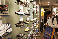 A teenager looks at Nike sneakers on display at a store in Shanghai, China..15 May 2005