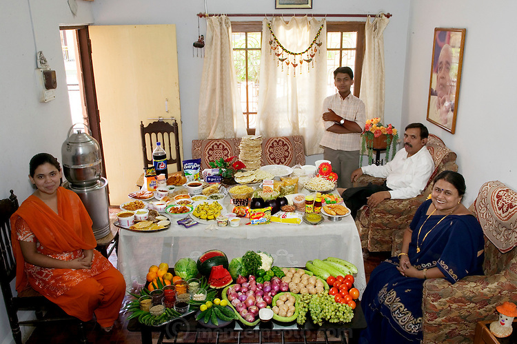 (MODEL RELEASED IMAGE). The Patkar family: Jayant, 48, Sangeeta, 42, daughter Neha, 19, and son Akshay, 15 in the living room of their home in Ujjain, Madhya Pradesh, India, with one week's worth of food. Cooking method: gas stove. Food preservation: refrigerator-freezer. /// The Patkar family is one of the thirty families featured in the book Hungry Planet: What the World Eats (p. 166). Food expenditure for one week: $39.27 USD. (Please refer to Hungry Planet book p. 167 for the family's detailed food list.)