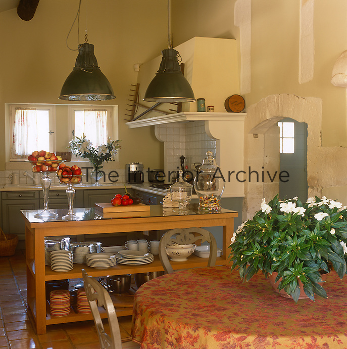A yellow country style kitchen with a tiled floor. The room has green fitted units and metal pendant lights.  Tableware and cooking pans are arranged on a wooden shelving unit.