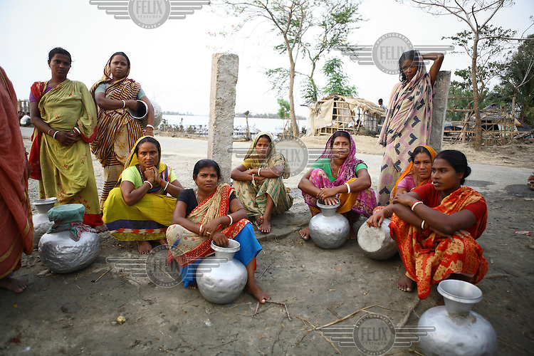 A group of women with their waterjugs. There are severe clean water shortages as floodwater becomes stagnant and polluted, contaminating existing water supplies. Thousands of people were displaced in Shyamnagar Upazila, Satkhira district after Cyclone Aila struck Bangladesh on 25/05/2009, triggering tidal surges and floods.