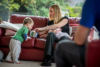 A woman sitting on a sofa breastfeeding her 2 month old baby while interacting with one of her older sons who is playing with a saucepan.<br /> <br /> Hampshire, England, UK<br /> 10/02/2013