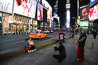 NEW YORK, NY - MARCH 19:  A man takes a picture of three girls in Time Square on March 19, 2020 in New York City. Gov Cuomo has ordered nonessential businesses in the state to close by 8 p.m. Sunday as more than 11,000 confirmed cases and 56 deaths. (Photo by Pablo Monsalve / VIEWpress via Getty Images)