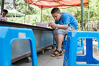 A boy prepares a fishing hook at a carnival game in Changle Park in Xian, Shaanxi, China.