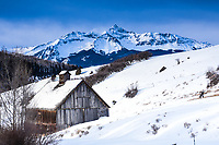 14.016 foot high Wilson Peak draped in winter's finest rises above an old barn high above Telluride, Colorado.