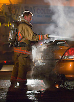A Columbus, Ohio, fire fighter extinguishes a car fire.<br />