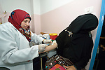 Rana Mashood, a lab technician, draws blood from a woman patient in a clinic in Shejaiya, a neighborhood of Gaza City that was hard hit by the Israeli military during the 2014 war. The clinic is run by the Department of Service for Palestinian Refugees of the Near East Council of Churches, a member of the ACT Alliance, and funded in part by the Pontifical Mission for Palestine.  This clinic has twice been destroyed by Israeli air strikes, but each time has been rebuilt by DSPR.