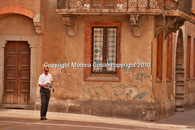 A man reading a newspaper on a street corner in Como, Italy on Lake Como