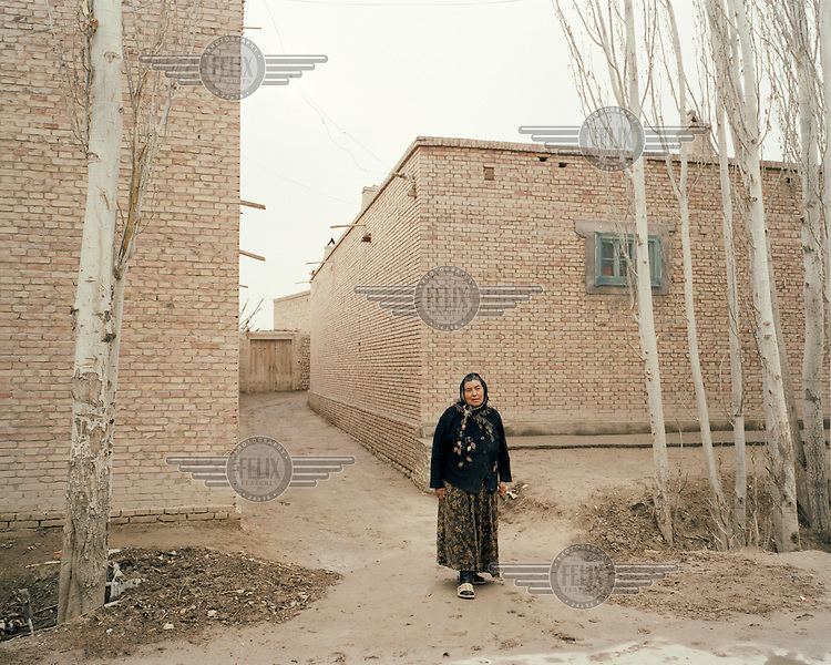 A Uighur (Uyghur) woman waits outside her house in Artux village.