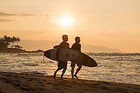As the sun sets, two surfers run down the beach to go surfing at Chun's Reef, with Ka'ena Point in the distance, North Shore, O'ahu.