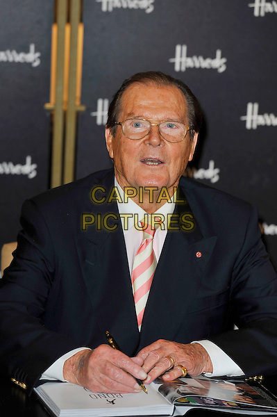 Sir Roger Moore.Photocall for the book signing of 'Bond On Bond', Harrods, Knightsbridge, London, England. .11th October 2012.book half length table sitting glasses white shirt pinks stripe tie black blue suit jacket mouth open.CAP/MAR.© Martin Harris/Capital Pictures.