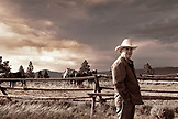 USA, Wyoming, Encampment, a man in a cowboy hat stands next to a fenceline with horses and an ominous sky in the distance