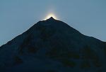 Sunrise illuminates a single peak in the Alaska Range.