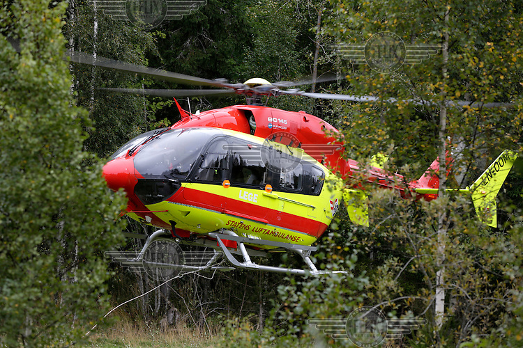 Helicopter from Norwegian Air Ambulance between trees.