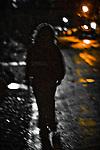 A young woman walking along a dark street at night