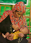 Shortly after they made the perilous crossing from Myanmar into Bangladesh, a woman feeds her child in a United Nations clinic for severely malnourished Rohingya children in the Balukhali Refugee Camp near Cox's Bazar, Bangladesh. She is using Plumpy'nut, a peanut-based supplement given to malnourished children.<br /> <br /> More than 600,000 Rohingya refugees have fled government-sanctioned violence in Myanmar for safety in this and other camps in Bangladesh..