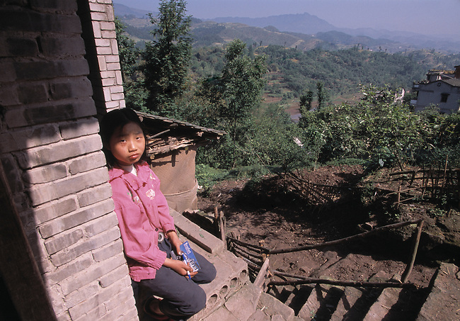 Young girl sits outside home above fertile valley; rural farm country; Ba culture; near Shibaozhai, China, Asia; 042003