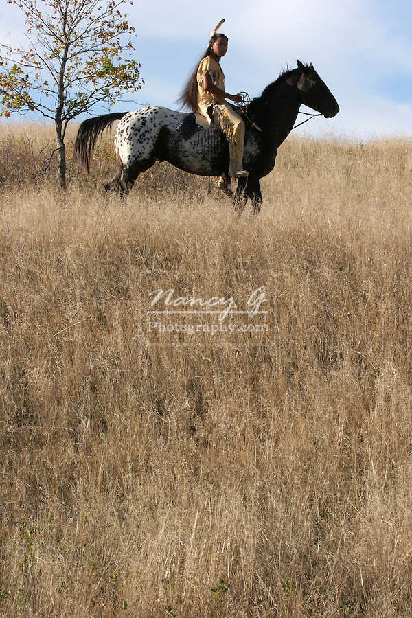 A Native American Indian man riding horseback on the prairie of South Dakota