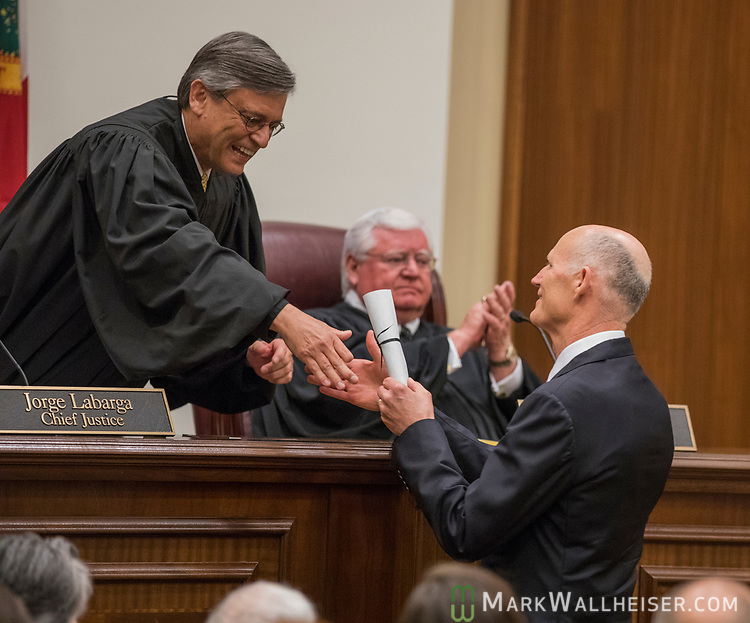 Florida Governor Rick Scott presents the nomination of Alan Lawson as the Florida Supreme Court's 86th justice to Chief Justice Jorge Lafarge during the investiture of the Honorable Alan Lawson in Tallahassee, Florida