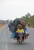 A motor Bike and a very big load with cans traveling on the rural highway near Battambang, Cambodia.