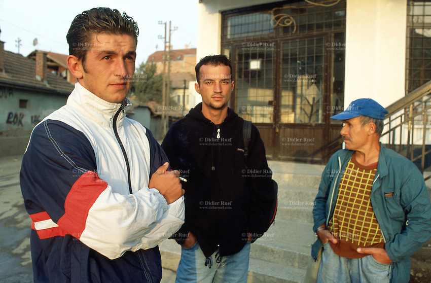 Kosovo. Pristina. Mr Florim Kunuschevci (first from the left) was a  heroin drug addict.  He is now clean (out of drugs) and waits in the early morning with other men for a day job.  © 2001 Didier Ruef