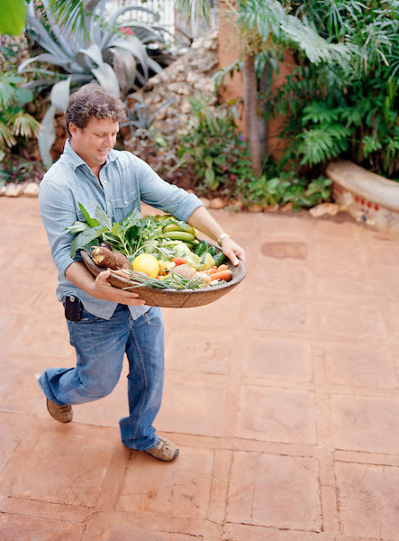 Jake's Resort owner Jason Henzell brings in a platter of organic fruits and vegetables from local farms to the kitchen at Jake's Resort. Treasure Beach, Jamaica.