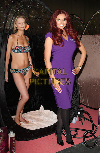 Amy Childs .appears at the Professional Beauty Show at Excel Centre, London, England..February 25th 2013.full length dress black tights model bikini hand on hip purple bottle .CAP/ROS.©Steve Ross/Capital Pictures..