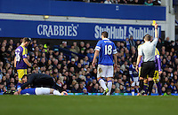 Pictured: Jordi Amat (R obscured) of Swansea sees a yellow card by match refereeKevin Friend (R) for his foul against an Everton player who is being seen to by the team physiotherapist.  Sunday 16 February 2014<br />