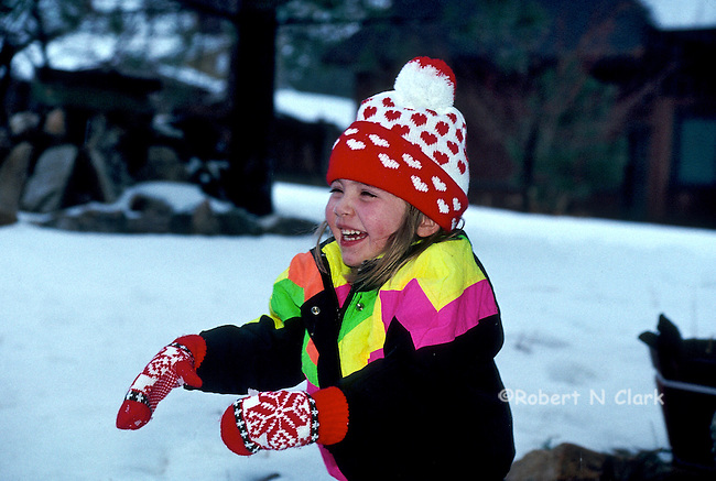 Girl in snow laughing with her hands raised