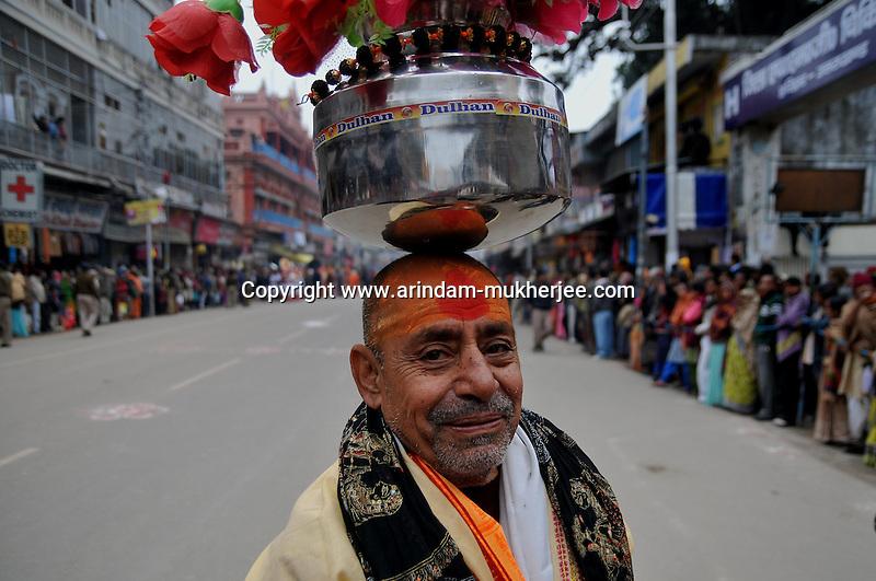 A holy man balances a Kumbh (round pot) on his head on the first Sahi Snan (Royal dip) day at Kumbh mela on 12th February 2010. Haridwar, Uttara Khand, India, Arindam Mukherjee