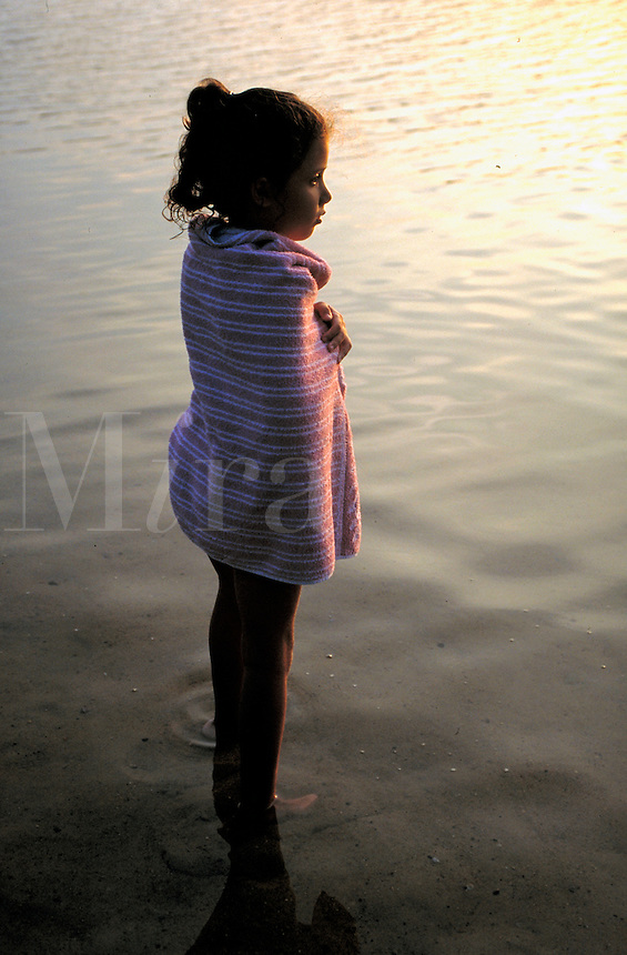 Young girl wrapped in a towl and standing in the lake water.