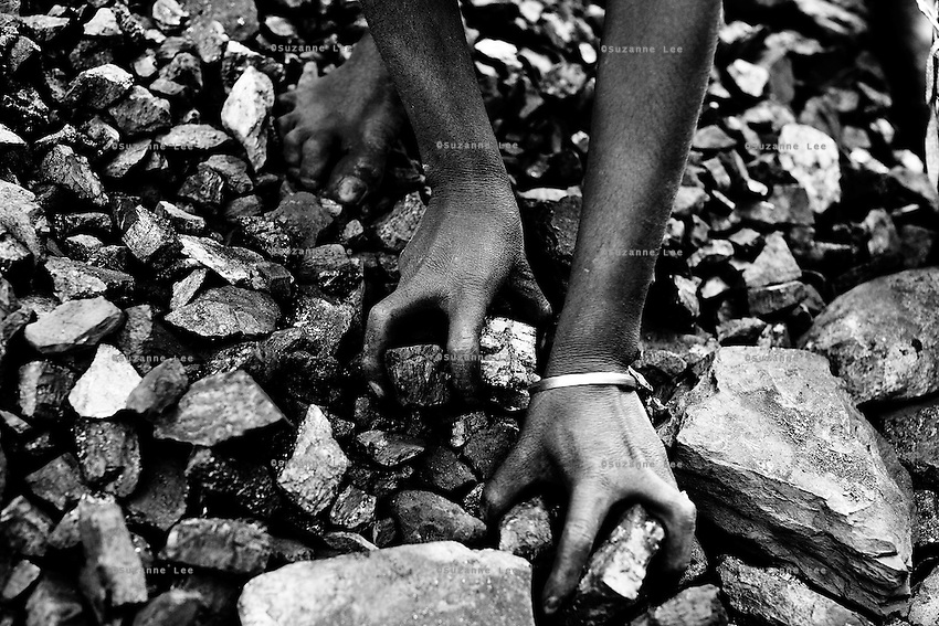 A young barefooted miner fills her basket with coal, and prepares to carry head-loads of heavy coal rocks for kilometers, across sharp stones and hot coals in the open-pit coalmines of Dhanbad, Jharkhand, India.