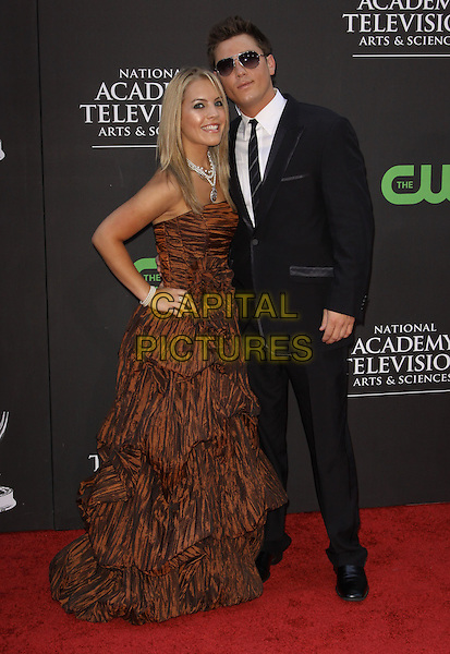 KRISTEN ALDERSON & BRANDON BUDDY.36th Annual Daytime Emmy Awards held At The Orpheum Theatre, Los Angeles, California, USA..August 30th, 2009.emmys full length brown gown dress black suit sunglasses shades pattern dress hand on hip .CAP/ADM/KB.©Kevan Brooks/AdMedia/Capital Pictures.