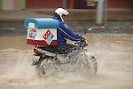 A Dominoes Pizza man makes his delivery on motorcycle, undeterred by driving rain and flooded roads in his Guatemalan town.