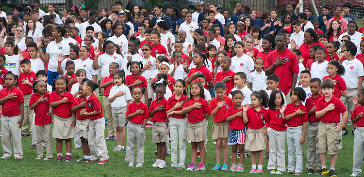 Students say the Pledage of Allegence during the opening of Memorial Day activities at The Rice School, May 26, 2014.