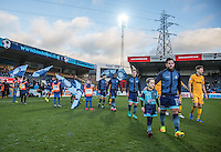 Sam Wood of Wycombe Wanderers heads onto the pitch with a young mascot during the Sky Bet League 2 match between Wycombe Wanderers and Newport County at Adams Park, High Wycombe, England on 2 January 2017. Photo by Andy Rowland.