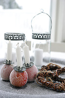 Glass lanterns and apples with Christmas candles make a festive display on the veranda table