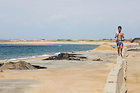 Patrick Teravainen, 12, of Sandwich, Mass., walks along a barrier blocking off a destroyed section of the parking lot at Herring Cove Beach in the Cape Cod National Seashore outside of Provincetown, Mass., USA, on Fri., July 1, 2016. Portions of the parking lot have been closed after land eroded during storms earlier this year. This was Patrick's first visit to the beach.