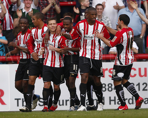 10/04/2010. Brentford players celebrate after forward Charlie MacDonald (3rd from left) hit home Brentford's first goal of the game from the penalty spot during the second half.  Division 1 match at Griffin Park, Brentford, London, England, UK