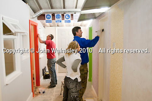 Painting & Decorating student watches an instructor apply paint with a brush, Able Skills, Dartford, Kent.