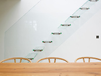 A glass staircase is outlined against the white wall of the dining area