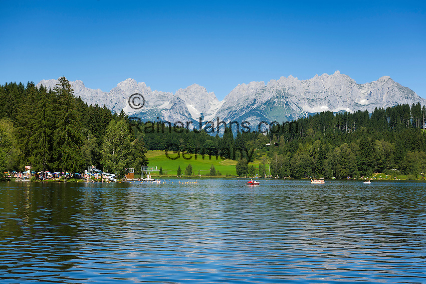 Austria, Tyrol, near Kitzbuhel: idyllic Schwarzsee (Black Lake) on the outskirts of Kitzbuhel, at background Wilder Kaiser mountains | Oesterreich, Tirol, bei Kitzbuehel: Schwarzsee, idyllisch gelegener Badesee, 8 ha gross und bis zu 8 m tief, einer der waermsten Seen der Alpen, im Hintergrund das Wilder Kaiser Gebirge