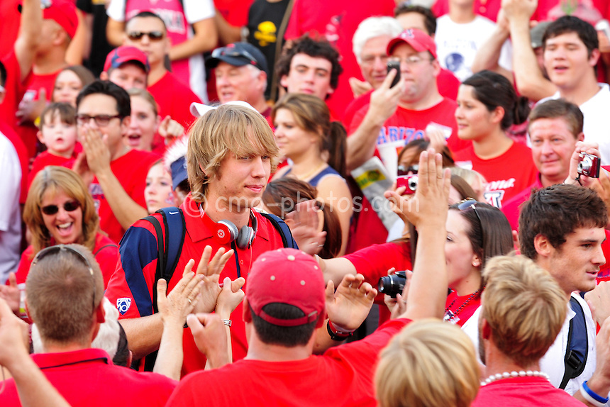 "ept 18, 2010; Tucson, AZ, USA; Arizona Wildcats quarterback Nick Foles walks through a crowd of fans during ""Wildcat Walk"" prior to a game against the Iowa Hawkeyes at Arizona Stadium."