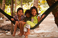 Three Cambodian girls in a hammock are not shy about posing for the camera