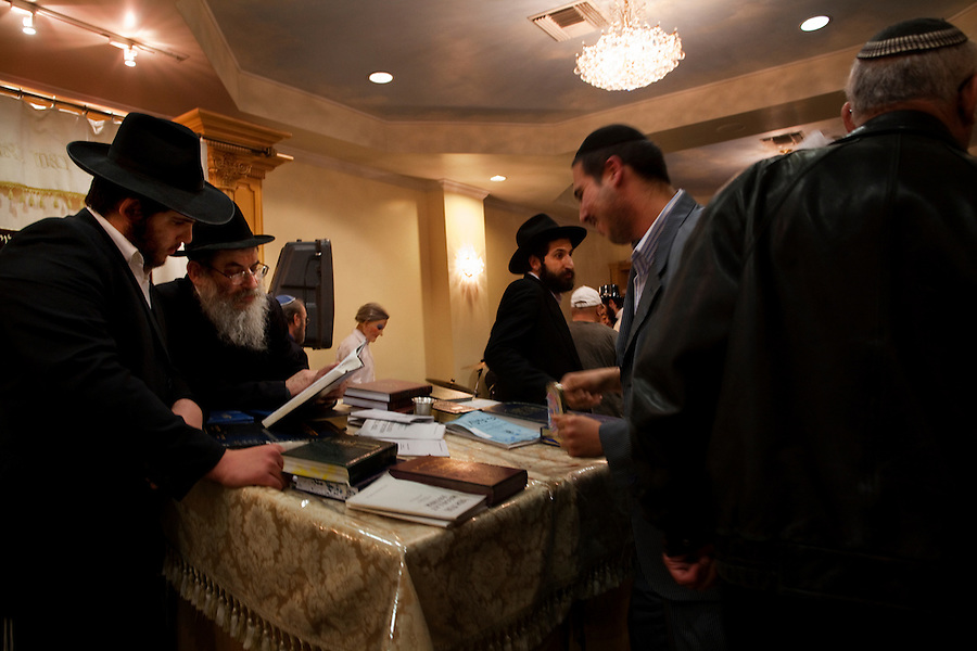 Los Angeles, California, March 19, 2011 - Members of the Chabad Persian Youth Center during a reading of the Megillah during the Jewish holiday Purim at the center...Purim is a Jewish holiday that commemorates the deliverance of the Jewish people living in the Persian Empire from genocide at the hands of the political advisor, Haman, to the Persian King Ahasuerus, as documented in the Talmud's Book of Esther. It is celebrated by the reading of the Scroll of Esther or the Megillah, sending food gifts to friends, giving charity to the poor and celebrating with a festive meal. During the reading of the Megillah, when Haman's name is mentioned (which happens 54 times) the congregation engages in loud roars and the use of rattles in an effort to blot out his name. Today children and some adults dress in costume and masquerade to celebrate Purim. The custom is believed to have originated during the 15th century by Italian Jews influenced by the Roman carnival. One idea for the costumes is that God disguised his presence behind many of the natural events that happened during Purim. .