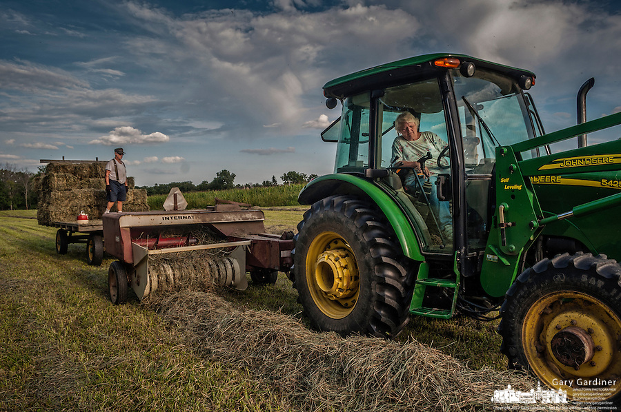 Connie Bigham drives the tractor as her husband, Sam , loads a trailer with fresh hay recently baled on his family's Westerville, OH, farm. Bigham's family has owned the farm since 1920 but recently signed a contingency contract to sell the land to a housing developer. It is the last working farm in the city.