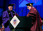 Helmut P. Epp, professor, former dean and former provost, receives a Via Sapientiae Award from David Miller, dean of the DePaul University College of Computing and Digital Media Sunday, June 11, 2017, during the DePaul University College of Computing and Digital Media and the College of Communication commencement ceremony at the Allstate Arena in Rosemont, IL. (DePaul University/Jamie Moncrief)