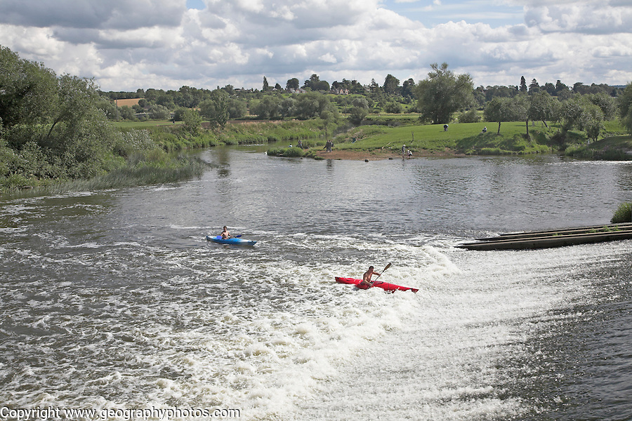 Canoeing in white water from the weir on the River Avon in the Vale of Evesham, Fladbury, Worcestershire, England